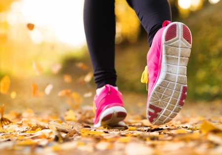 22902640 - close up of feet of a runner running in autumn leaves training exercise